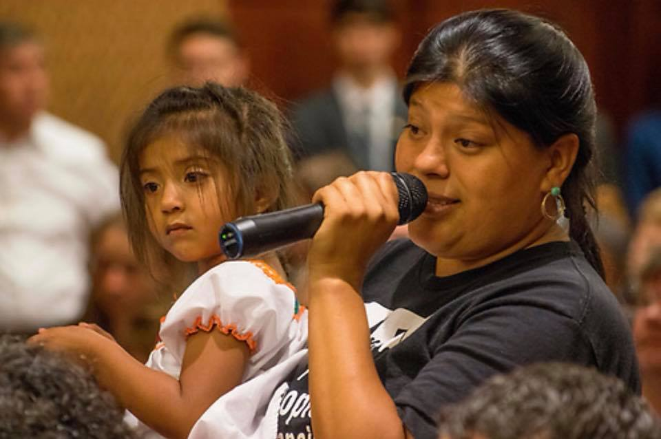 A woman speaks into a microphone while a little girl sits on her lap